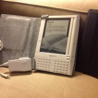Photo of the First Generation Kindle with its bundled leather case and power supply